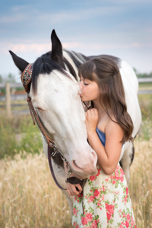 A young girl and her black and white horse