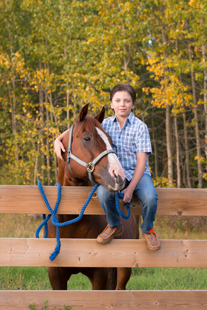 A boy posing for his portrait with his horse