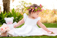 Baby in the park wearing a flower crown and white dress