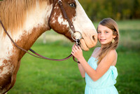 A girl in a blue dress pictured with her horse