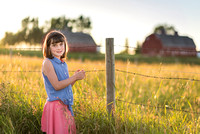 A girl in a field near a red barn at sunset