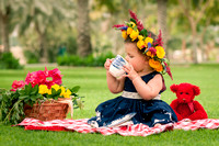 Little girl having tea at a picnic with a red bear and flower crown